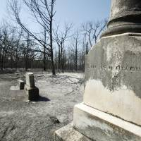 Photo -  Grave markers stand in the center of the charred Wright's Cemetery after Tuesdays wildfires swept through the area in Oklahoma City , Wednesday, August 31, 2011. Photo by Steve Gooch ORG XMIT: KOD