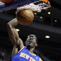 Photo - New York Knicks forward Amare Stoudemire (1) dunks against the Detroit Pistons during the first half of an NBA basketball game Wednesday, March 6, 2013, in Auburn Hills, Mich. (AP Photo/Duane Burleson)