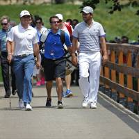 Photo - Rory McIlroy, of Northern Ireland, left, and Sergio Garcia, of Spain, walk along the foot bridge on the fourth hole during a practice round for the PGA Championship golf tournament at Valhalla Golf Club on Tuesday, Aug. 5, 2014, in Louisville, Ky. The tournament is set to begin on Thursday. (AP Photo/Mike Groll)