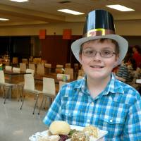 Photo - Volunteer Brenton Fairchild, 11, carries a meal to a table at Norman's Community Thanksgiving Dinner. PHOTO BY CONNIE HEFNER, FOR THE OKLAHOMAN  Connie Hefner