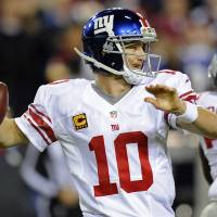 Photo - New York Giants quarterback Eli Manning (10) passes the ball during the first half of an NFL football game against the Washington Redskins in Landover, Md., Monday, Dec. 3, 2012. (AP Photo/Nick Wass)