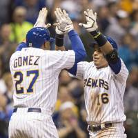 Photo - Milwaukee Brewers' Aramis Ramirez gets a high-five from teammate Carlos Gomez after hitting a two-run home run off Pittsburgh Pirates' Francisco Liriano during the fourth inning of a baseball game on Friday, April 11, 2014, in Milwaukee. (AP Photo/Tom Lynn)