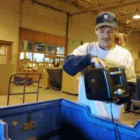 Photo - Leon Castillas inspects a toaster that was dropped off as a donation at the Goodwill Donation Center at the Green River Road location in Evansville, Ind. on Wednesday morning, Nov. 28, 2012. Castillas, a veteran of the U.S. Army, is one of the first participants to complete the Vanderburgh County's Veterans Treatment Court this year.    (AP Photo/The Evansville Courier & Press, Erin McCarken)