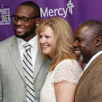 Photo - From left, Gerald McCoy of the Tampa Bay Buccaneers, Laurie Applekamp, state director of the March of Dimes, and Gerald McCoy, Sr., pose for a photo during the March of Dimes Sports Headliner Awards Banquet at the Chickasaw Bricktown Ballpark in Oklahoma City, Thursday, June 20, 2013. Photo by Nate Billings, The Oklahoman
