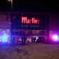 Photo - CORRECTS BYLINE - Elkhart Police, the Elkhart Fire Department, Indiana State Police and emergency personnel respond to reports of a shooting inside Martin's Supermarket in Elkhart, Ind., about 10:30 p.m. Wednesday, Jan. 15, 2014. Three people, including the gunman, died Wednesday night after a shooting at an Elkhart grocery store. (AP Photo/Truth, Larry Tebo)