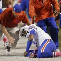 Photo - A trainer rushes to help Buffalo Bills quarterback EJ Manuel after he was injured on a third-quarter run against the Cleveland Browns in the third quarter of an NFL football game Thursday, Oct. 3, 2013, in Cleveland. (AP Photo/Tony Dejak)