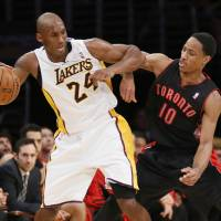 Photo - Los Angeles Lakers' Kobe Bryant, left, dribbles the ball as he is defended by Toronto Raptors' DeMar DeRozan, right, during the second half of an NBA basketball game in Los Angeles, Sunday, Dec. 8, 2013.  It was Bryant's first game back after a torn left Achilles tendon injury. (AP Photo/Danny Moloshok)