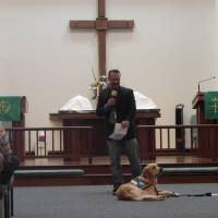 Photo - Above:  Koey   Keylon, a member of St. Mark Lutheran Church in Edmond, with Rufus Comfort Dog, talks about the Lutheran Church Charities Comfort Dog Program at the Aug. 24 worship service at the church.  Photo by Mandy Long, for The Oklahoman