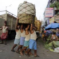 Photo - Indian laborers carry a load pf vegetables at a wholesale market in Kolkata, india, Wednesday, July 9, 2014. India's new government presents its inaugural budget this week in the first substantive test of whether Prime Minister Narendra Modi will deliver on ambitious promises to revive stalled economic growth. India's economic growth has slowed to less than 5 percent for the last two years after a decade of expanding by an average of 8 percent, which is the minimum the government says is necessary to provide jobs for the 13 million young Indians who enter the workforce each year. (AP Photo/ Bikas Das)