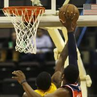 Photo - Washington Wizards point guard John Wall, right, blocks a shot by Cleveland Cavaliers point guard Kyrie Irving, left, in the first half of an NBA preseason basketball game on Wednesday, Oct. 23, 2013, in Cincinnati. (AP Photo/Al Behrman)