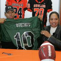 Photo - LETTER OF INTENT / HIGH SCHOOL FOOTBALL / SIGNING DAY / SIGN / PARENT / FAMILY: Douglass High School's Destin Stewart signs holds up a University of Hawaii jersey with his mother Sabena Watts looks on in Oklahoma City, Oklahoma February 4, 2009.  BY STEVE GOOCH, THE  OKLAHOMAN.  ORG XMIT: KOD