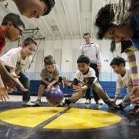 Photo - Above: Children participate in a game of stride ball, a game in which players stand in a circle and someone in the  middle tries to roll the ball between the legs of the other players, Thursday during a city-sponsored spring break camp in Norman. School  resumes on Monday.