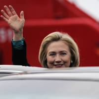 Photo -   U.S. Secretary of State Hillary Clinton waves as she arrives at the airport in Cartagena, Colombia Friday April 13, 2012. Leaders of the western hemisphere will attend the 6th Summit of the Americas in Cartagena this weekend. (AP Photo/John Vizcaino, Pool)