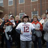 Photo - Tucker Holloway, 9, of Yukon, Okla., is surrounded by OSU fans during the Spirit Walk before the Bedlam college football game between the Oklahoma State University Cowboys (OSU) and the University of Oklahoma Sooners (OU) at Boone Pickens Stadium in Stillwater, Okla., Saturday, Dec. 3, 2011. Photo by Sarah Phipps, The Oklahoman