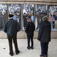 Photo - Richard Bamforth, left, his wife Pat Bamforth, right, and their granddaughter, Pippa Adam, look at a mural depicting Maine's labor history on Monday, Jan. 14, 2013, in Augusta, Maine. The mural was put on  public display in the atrium leading to the Maine State Museum 22 months after Gov. Paul LePage ordered it removed from the Labor Department lobby. (AP Photo/Clarke Canfield)