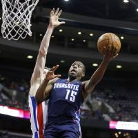 Photo - Charlotte Bobcats guard Kemba Walker (15) goes to the basket against Detroit Pistons forward Kyle Singler in the first half of an NBA basketball game, Sunday, Jan. 6, 2013, in Auburn Hills, Mich. (AP Photo/Duane Burleson)