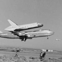 Photo -   FILE - In this Feb. 18, 1977 file photo, America's Space Shuttle Enterprise, rides atop a giant 747 on its first test flight at Edwards Air Force Base, Calif. Enterprise is scheduled to arrive in New York on the back of a NASA jumbo jet on Friday, April 27, 2012, where it will be stored in an hangar at John F. Kennedy International Airport before assuming its new permanent location on the deck of the Intrepid Air and Space Museum in New York Harbor. (AP Photo)