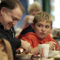 Photo - Greg Roberts and son Drew, 10, dine together Thursday at the annual Police-Fire Chili Supper that raises money for the Cleveland County Christmas Store. PHOTO BY STEVE SISNEY, THE OKLAHOMAN  STEVE SISNEY
