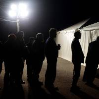 Photo - Under the lights of a generator, voters wait in line outside of a tent serving as a polling site in the Midland Beach section of Staten Island, New York, on Election Day Tuesday, Nov. 6, 2012. The original polling site, a school, was damaged by Superstorm Sandy. (AP Photo/Seth Wenig) ORG XMIT: NYSW101