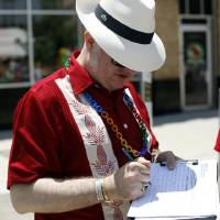 Photo - David Macey signs a petition Saturday during the 2012 OKC Pride Festival in downtown Oklahoma City.  Photo by Sarah Phipps,  The Oklahoman
