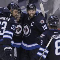Photo - Winnipeg Jets' Dustin Byfuglien (33), Bryan Little, Andrew Ladd (16) and Jacob Trouba (8) celebrate Byfuglien's overtime goal that gave the Jets a 5-4 win over the Toronto Maple Leafs in an NHL hockey game Saturday, Jan. 25, 2014, in Winnipeg, Manitoba. (AP Photo/The Canadian Press, Jason Woods)