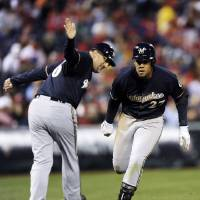 Photo - Milwaukee Brewers' Carlos Gomez (27) is greeted by third base coach Ed Sedar and scores on a solo home run in the fourth inning of a baseball game against the Philadelphia Phillies, Wednesday, April 9, 2014, in Philadelphia. (AP Photo/Michael Perez)