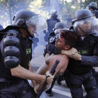 Photo - Police arrest a demonstrator during an Anti-World Cup protest near Maracana stadium where the final World Cup game is taking place in Rio de Janeiro, Brazil, Sunday, July 13, 2014. For the final match between Argentina and Germany, authorities deployed the largest security detail in Brazil's history. (AP Photo/Leo Correa)