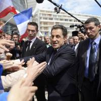 Photo -   France's President and conservative candidate for re-election in 2012, Nicolas Sarkozy, shakes hands with crowds of supporters after a campaign meeting in Sables d'Ollonne, western France, Friday, May 4, 2012. The final polls before France's presidential election Sunday show a shrinking gap between President Nicolas Sarkozy and Socialist challenger Francois Hollande, but still predict a Hollande victory. (AP Photo/Eric Feferberg, Pool)