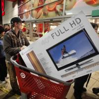Photo - Ryan Martin pushes his door buster purchase from the store last year after Target's midnight opening on Black Friday. Consumers spent an average of $400 during the Black Friday weekend last year.Photo by STEVE SISNEY, THE OKLAHOMAN Archives