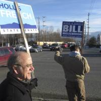 Photo -   Alaska state Sens. Hollis French, left, and Bill Wielechowski, both Anchorage Democrats, wave signs during a lunch hour rally to support members of the Senate's bipartisan coalition. French is being challenged by Republican Bob Bell, while Republican Bob Roses is trying to unseat Wielechowski. (AP Photo/Mark Thiessen)