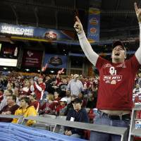 Photo - Russell Daniels, originally from Enid but now living in Phoenix, cheers during the Fiesta Bowl college football game between the University of Oklahoma Sooners and the University of Connecticut Huskies in Glendale, Ariz., at the University of Phoenix Stadium on Saturday, Jan. 1, 2011.  Photo by Bryan Terry, The Oklahoman