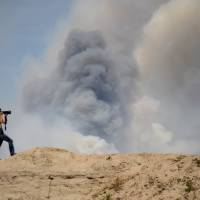 Photo - A photographer takes photos of the Black Forest Fire as it burns out of control for a second straight day near Colorado Springs, Colo. on Wednesday, June 12, 2013. Three Colorado wildfires fueled by hot temperatures, gusty winds and thick, bone-dry forests have together burned dozens of homes and led to the evacuation of more than 7,000 residents and nearly 1,000 inmates at medium-security prison. (AP Photo/Bryan Oller)