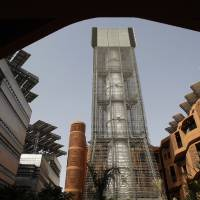 Photo -   FILE - In this Sunday, Jan. 16, 2011 file photo, the 45 meter height Wind Tower brings upper level wind to the public square at the Masdar Institute campus as a part of Masdar City in Abu Dhabi, United Arab Emirates. Hosting the climate talks is the latest bid by Qatar to flex its muscles on the international stage, following its successful bid to host the 2022 World Cup and its backing of Libyan and Syrian rebels. (AP Photo/Kamran Jebreili, File)