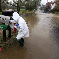 Photo - Sandy LeDuc braves floodwaters to gather her mail on Piner Road, Friday Dec. 21, 2012 in Santa Rosa, Calif as a large winter storm barreled in to Northern California. (AP Photo/The Press Democrat, Kent Porter)