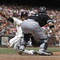 Photo - Chicago White Sox catcher Tyler Flowers, right, reaches to tag San Francisco Giants' Gregor Blanco, who was originally ruled out at home but then ruled safe after review, during the seventh inning of a baseball game in San Francisco, Wednesday, Aug. 13, 2014. (AP Photo/Jeff Chiu)
