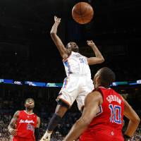 Photo - Oklahoma City's Kevin Durant (35) loses control of the ball between Los Angeles Clippers' Mo Williams (25) and Eric Gordon (10)during the NBA basketball game between the Oklahoma City Thunder and the Los Angeles at the Oklahoma City Arena, Wednesday, April 6, 2011. Photo by Bryan Terry, The Oklahoman