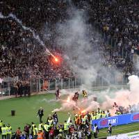 Photo - Napoli fans throw flares prior to the start of Italian Cup final match between Fiorentina and Napoli in Rome's Olympic stadium Saturday, May 3, 2014. At least one fan and one police officer were reportedly shot before the Italian Cup final between Napoli and Fiorentina, and the fan was in serious condition. As a result, the start of the final was delayed, and there were scenes of violence inside the stadium with a firefighter injured by fireworks thrown from the stands. The shootings occurred in an area where Napoli fans were gathering for the match, the ANSA news agency reported. (AP Photo/Marco Rosi, Lapresse) ITALY OUT