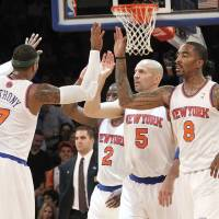 Photo - New York Knicks' Carmelo Anthony (7) high fives team mates Raymond Felton (2) Jason Kidd (5) and J.R. Smith (8) during the first half of an NBA basketball game against the Washington Wizards, Tuesday, April 9, 2013, at Madison Square Garden in New York.  (AP Photo/Mary Altaffer)