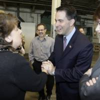Photo -   Gov. Scott Walker shakes hands with people after discussing his Transform Milwaukee project at the Hatco Corporation Storage Warehouse on South 28th Street in Milwaukee on Monday, April 30, 2012. Walker announced the $100 million
