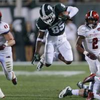 Photo - Michigan State wide receiver Macgarrett Kings Jr. (85) jumps to elude Jacksonville State defenders during the second half of an NCAA college football game in East Lansing, Mich., Friday, Aug. 29, 2014. (AP Photo/Paul Sancya)