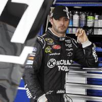 Photo -   Jimmie Johnson looks at his car in the garage during practice for the NASCAR Sprint Cup Series auto race at Chicagoland Speedway in Joliet, Ill., Friday, Sept. 14, 2012. (AP Photo/Nam Y. Huh)