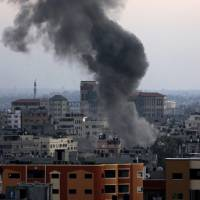 Photo - Smoke and dust rise after an Israeli strike hit Gaza City in the northern Gaza Strip, Wednesday, Aug. 20, 2014. (AP Photo/Adel Hana)