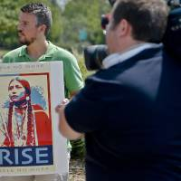 Photo - Dustin Cornell carries a sign supporting Dusten Brown's custody rights during Monday's rally at the state Capitol. PHOTO BY CHRIS LANDSBERGER, THE OKLAHOMAN  CHRIS LANDSBERGER - Photo by Chris Landsberger, The