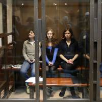 Photo -   Feminist punk group Pussy Riot members, from left, Maria Alekhina, Yekaterina Samutsevich and Nadezhda Tolokonnikova sit in a glass cage at a court room in Moscow, Wednesday. Oct. 10, 2012. Three members of the punk band Pussy Riot are set to make their case before a Russian appeals court that they should not be imprisoned for their irreverent protest against President Vladimir Putin. Their impromptu performance inside Moscow's main cathedral in February came shortly before Putin was elected to a third term. The three women were convicted in August of hooliganism motivated by religious hatred and sentenced to two years in prison. (AP Photo/Sergey Ponomarev)