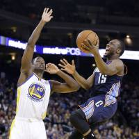Photo - Charlotte Bobcats' Kemba Walker (15) scores against Golden State Warriors' Harrison Barnes (40) during the first half of an NBA basketball game in Oakland, Calif., Tuesday, Feb. 4, 2014. (AP Photo/Tony Avelar)