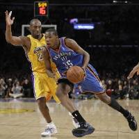 Photo - Los Angeles Lakers' Kobe Bryant, left, pressures Oklahoma City Thunder's  Kevin  Durant during the first half of their NBA basketball game in Los Angeles, Tuesday, Dec. 22, 2009. (AP Photo/Jae C. Hong)