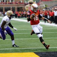 Photo - Maryland quarterback C.J. Brown (16) scores a touchdown past James Madison linebacker Rhakeem Stallings (7) during the first half of an NCAA college football game, Saturday, Aug. 30, 2014, in College Park, Md. (AP Photo/Nick Wass)