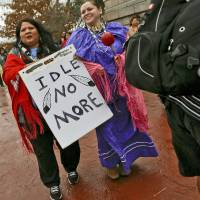 Photo - Carmen Thompson and Paulette Blanchard, from left, carries signs during a rally on the north side of the state Capitol for Native American rights on Monday, Jan. 28, 2013, in Oklahoma City, Okla.  Photo by Chris Landsberger, The Oklahoman