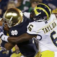 Photo -   Notre Dame's TJ Jones makes a catch against Michigan's Raymon Taylor during the first half of an NCAA college football game Saturday, Sept. 22, 2012, in South Bend, Ind. (AP Photo/Darron Cummings)