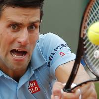 Photo - Serbia's Novak Djokovic returns the ball to Croatia's Marin Cilic during their third round match of  the French Open tennis tournament at the Roland Garros stadium, in Paris, France, Friday, May 30, 2014. (AP Photo/Michel Spingler)